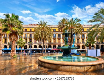 Royal area in Barcelona, Spain. Fountain with statues and high palm trees among traditional Spanish architecture at main central square of old town. Summer landscape with blue sky and clouds.