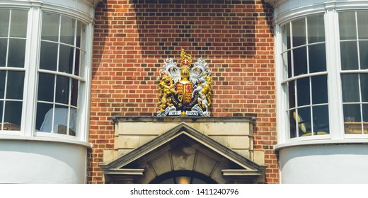 Royal Arms of England above Door Pediment, Coat of Arms between windows against red brick wall