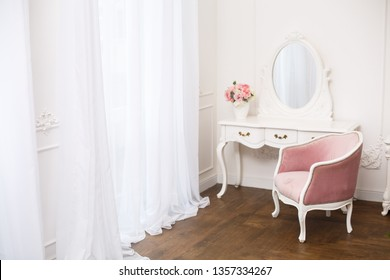 Royal bedroom. Boudoir room with pink soft armchair. Elegant white dressing table in light classic luxury interior