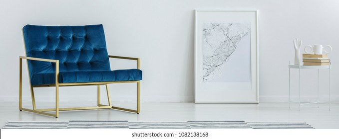 Royal blue armchair with gold frame standing in white room interior with map poster on the floor and small table with books