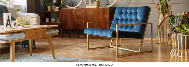 Royal blue armchair with gold frame standing in vintage living room interior with wooden cupboard and coffee table with magazines