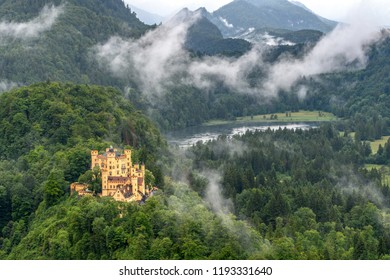 The Royal castle on the shore of a mountain lake. The forest-covered mountains against the stormy sky and fog.