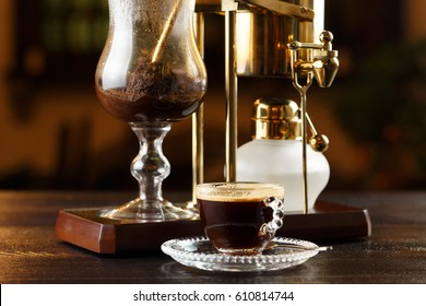 Royal coffee in siphon. The golden royal siphon. Making coffee. Freshly brewed coffee. Cup of coffee.