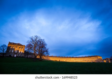 Royal Crescent in Bath, lit by the warm evening light with a stormy looking sky.
