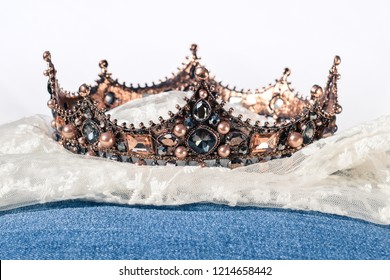 A royal crown on lace and blue jeans cloth wedding or nobility decoration