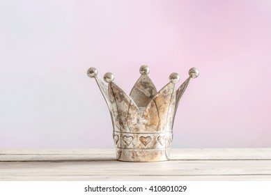 Royal crown on a wooden table on a pink background