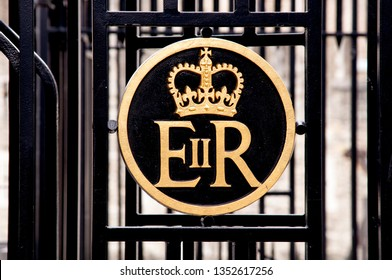 The Royal cypher of Queen Elizabeth II is the ER II with a crown above in a circle all in gold on a black background.
