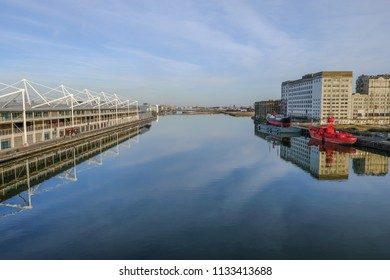 Royal Dock, London, UK - February 16, 2018: Side view of Excel exhibition centre and Royal docks on a still calm day with beautiful reflections.