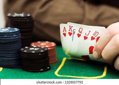 Royal flash with chip cards on the table. Poker game.Man's hand wih royal flash