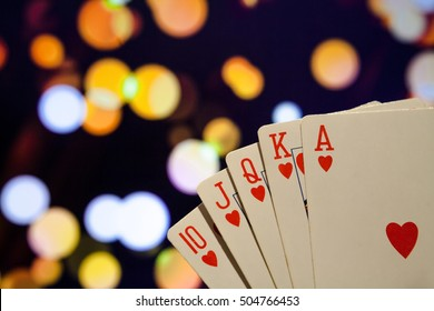 Royal flush hearts poker cards combination on blurred background casino game fortune