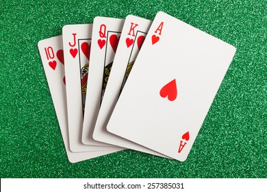 Royal flush. Playing cards isolated on a green background