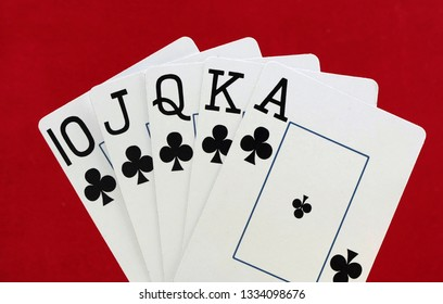 Royal flush playing cards on red felt background
