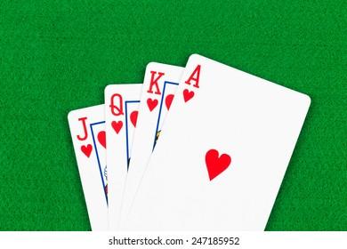 Royal flush poker playing cards on green felt background