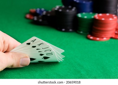 A royal flush in spades with poker chips in the background