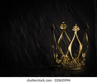 Royal gold crown on dark stone surface. Concept of wealth, success and kingdom.