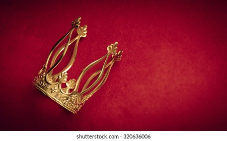 Royal gold crown on red velvet with copy space. Concept of wealth, success and kingdom.