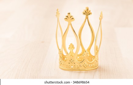 Royal gold crown on wooden surface. Concept of wealth, success and kingdom.