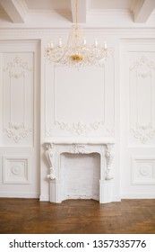 Royal interior in white colors. Elegant white fireplace in beautiful white room. White hall with fireplace