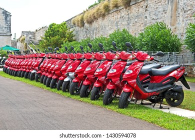 Royal Naval Dockyard, Bermuda - June 16 2019: A row of bright red scooters are for rent to tourists visiting Bermuda.