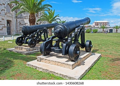 Royal Naval Dockyard, Bermuda - June 16 2019: two vintage cannon look out over the Victualling Yard with the Commissioners House and the Keep in the background.