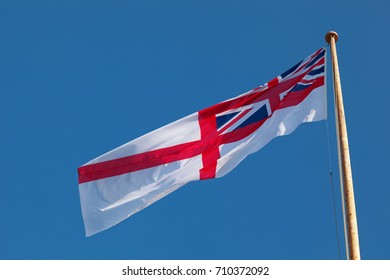 Royal navy ensign flying in the wind on a sunny day with a blue sky and space for text.
