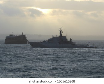 The Royal Navy River class patrol vessel HMS Tyne leaves Portsmouth Harbour for duties. Passes the  Spitbank Fort, a sea fort. Cloudy day at sunset. Rough seas.