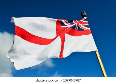 Royal Navy white ensign flying from a warship while docked.