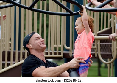 Royal Oak, Michigan - Father and Daughter, father is holding daughter, on playground equipement, annual Woodside Royal Oak Summer Picnic, June 25, 2018,