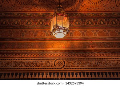 Royal Palace in Marrakech, Morocco, Africa - January 16, 2014: Old lamp lit in Arabic style and background a wall with details made by hand