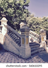 Royal palace staircase in the backyard with white and yellow columns and a geometric mosaic floor, surrounded by green trees in a beautiful sunny day with blue sky