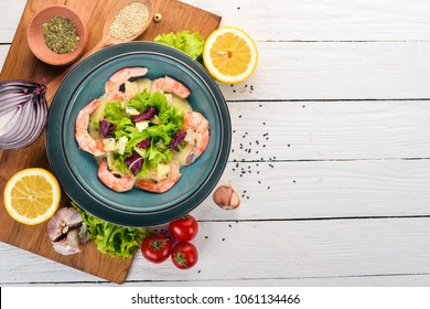 Royal prawns in creamy sauce and cheese. Seafood on a plate. Top view. On a white wooden background. Copy space.