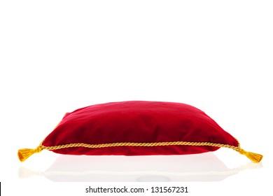 almohada de terciopelo rojo real con cuerda dorada aislada sobre fondo blanco