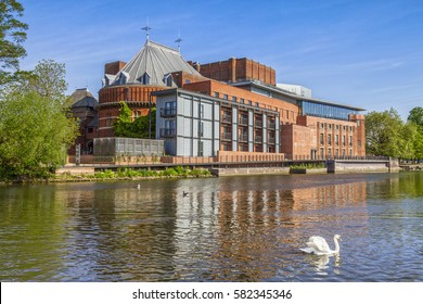 The Royal Shakespeare Theatre, home of the Royal Shakespeare Company, reflecting in the River Avon, with a swan in the foreground.