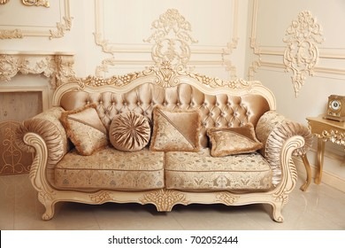 Royal sofa with pillows in beige luxurious interior with ornament frame wall