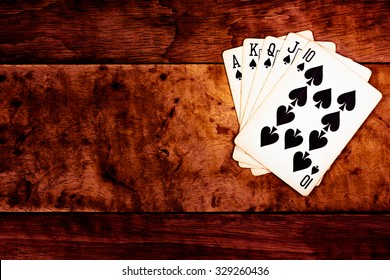 royal straight flush casino card games  over rough grunge wood texture background on desk or table dark tone style / winner,lucky,success