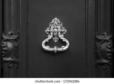 Royal style doorknocker on wooden door. Black and white.