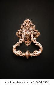 Royal style golden doorknocker on black wooden door.