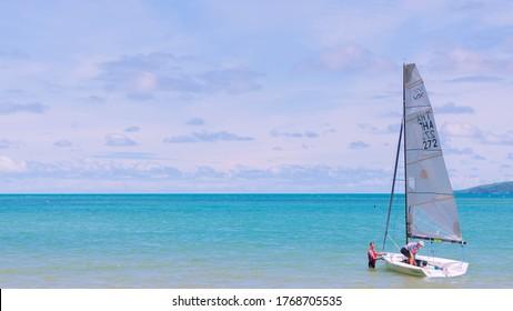 Royal Varuna Yacht Club: Pattaya Thailand, 27 June 2020 : Two men are preparing a sailboat to sail to the sea on a hot day.