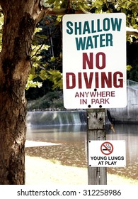 "Royalty Free Photograph - Isolated Photograph of ""Shallow Water - No Diving Sign"" in a community park's Swimming Area."