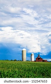 Royalty-free stock image of a Vermont farm with red barn and silo at the end of a corn field with storm clouds above and copy space at the top.