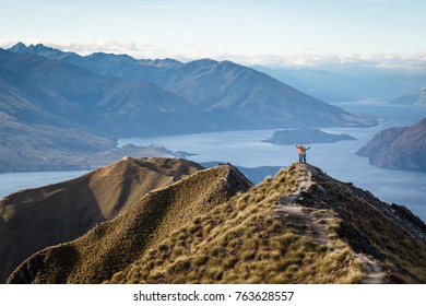 ROYS PEAK, WANAKA NEW ZEALAND APRIL 15 2017: two unidentified hikers are on the summit with lake Wanaka and the Alps in the background