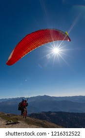 Roza Khutor (Sochi), Russia - 10 19 2018: Paraglider taking off with pilot/instructor and a tourist against the sun from the Roza Peak at over 2.300 mt over sea level. Sun visible under the sail