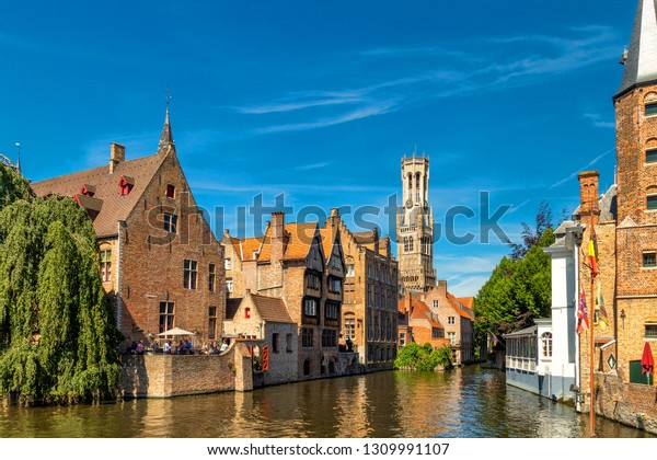 The Rozenhoedkaai canal in Bruges with the belfry in the background. Typical view of Bruges (Brugge), Belgium with red brick houses with triangle shaped roofs and canals.