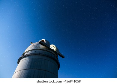 Rozhen, Bulgaria - July 15, 2016: Rozhen astronomical observatory under the night sky stars. Blue sky with hundreds of stars of the Milky way. Bulgarian National Astronomical Observatory.