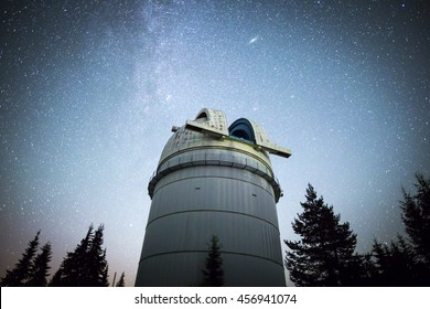 Rozhen, Bulgaria - July 15, 2016: Rozhen astronomical observatory under the night sky stars. Blue sky with hundreds of stars of the Milky way. Observatory in a pine trees forest in the mountain. .