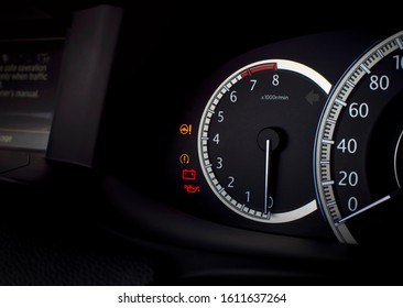 Rpm gauge and warning light such as electric steering, battery, engine oil lubricant on a mileage dashboard in a luxury car, automotive part concept.