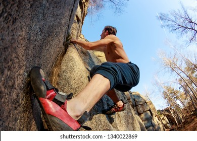 rrock shoe close-up of a rock climber climbs a boulder over a rock without insurance