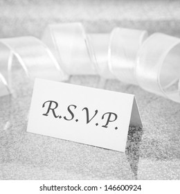 R.S.V.P. place card shot against a silver glittery background with shallow depth of field.