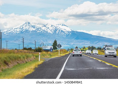 Ruapheu, New Zealand - December 15, 2017: Vehicles travelling along State Highway One on the North Island entering the Ruapehu district with view of the land mark volcanic mountain.