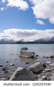 Ruataniwha Inlet foreshore at low tide with snow on top distant mountains under dramaitc clouds at Collingwood, Tasman Bay New Zealand.